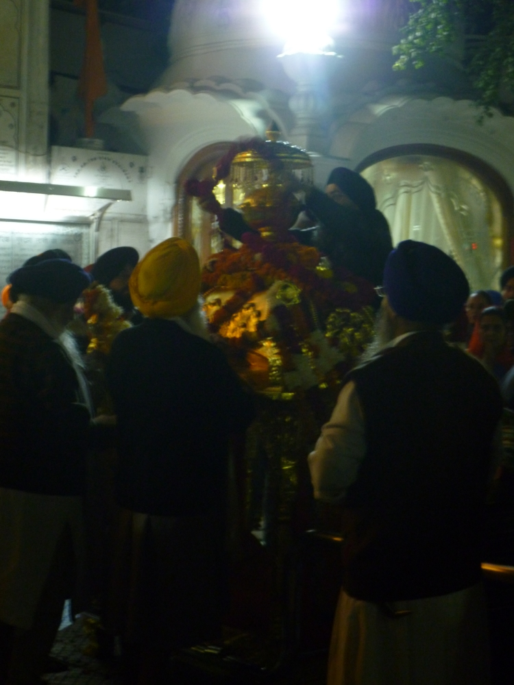Ceremony to put the Sikh holy book to bed. A palanquin is loaded up with pillows and garlands of flowers and perfume, into which the book is places and carried into its bedroom, while everyone sings, beats drums and plays the trumpet.