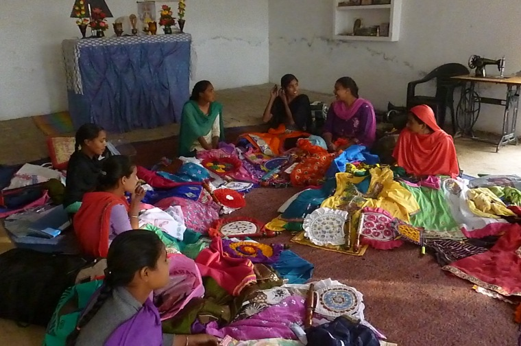 The girls from the six month tailoring training course showing the clothes they've made