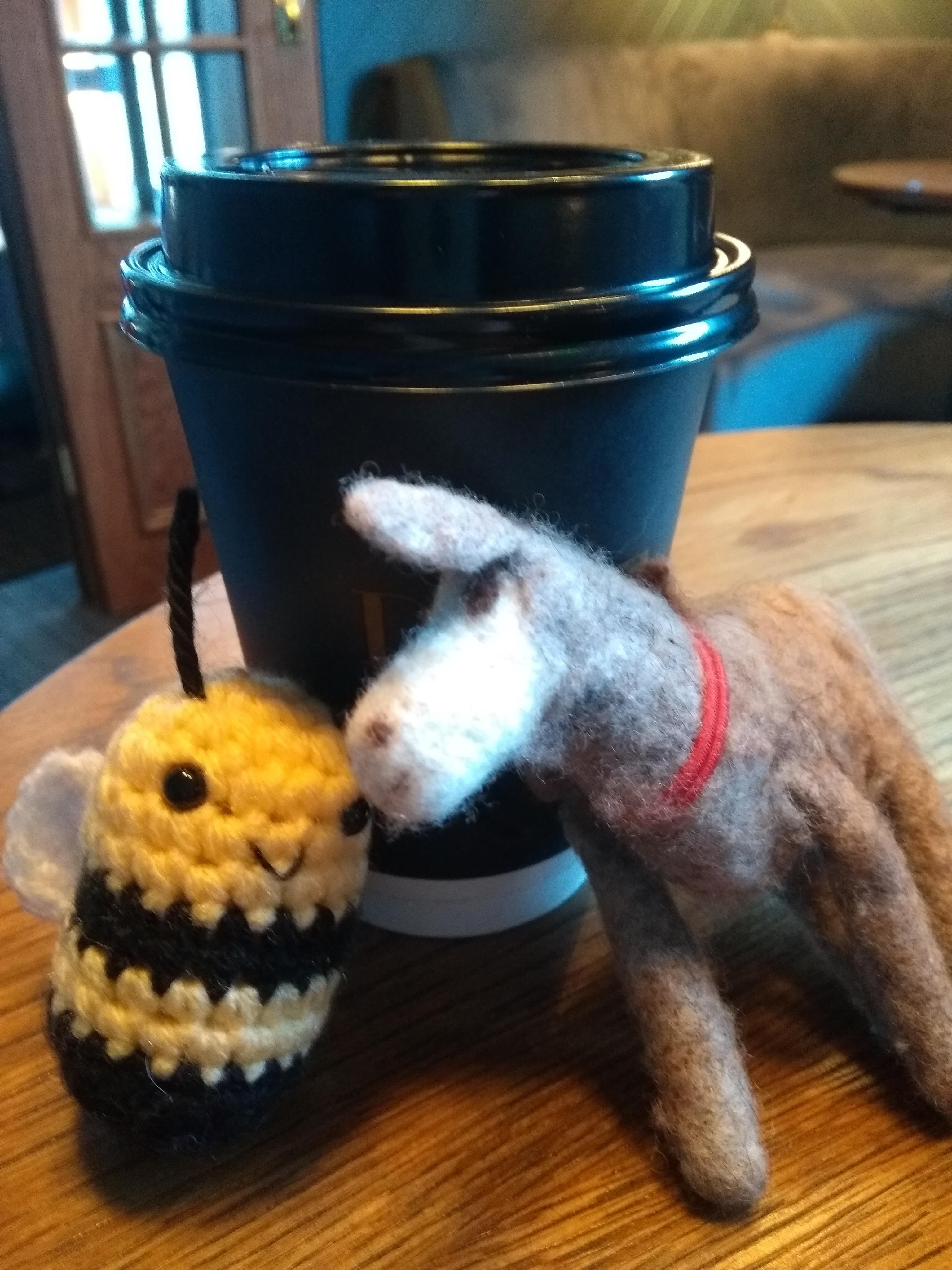 knit bee and felt donkey leaning up against black to go coffee cup